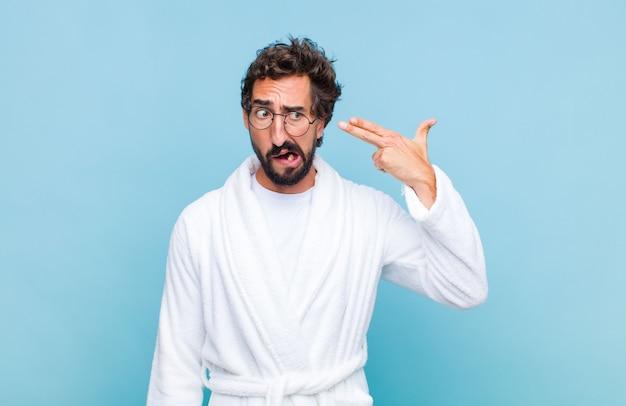 Jovem barbudo vestindo um roupão de banho, parecendo infeliz e estressado, gesto suicida fazendo sinal de arma com a mão, apontando para a cabeça