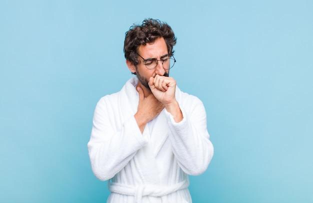 Jovem barbudo, vestindo um roupão de banho, sentindo-se doente, com dor de garganta e sintomas de gripe, tosse com a boca coberta