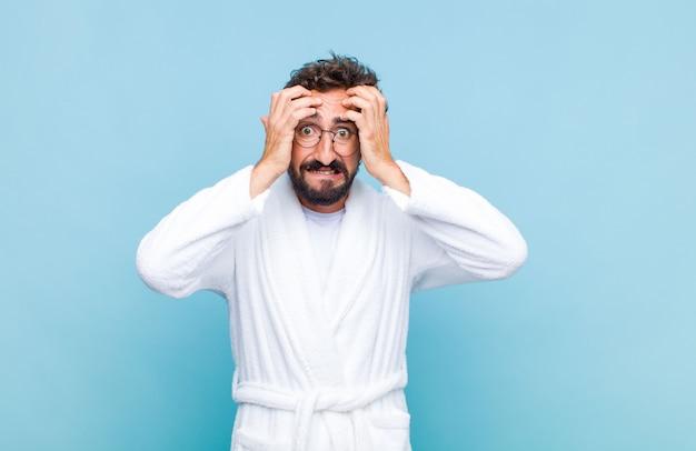 Jovem barbudo, vestindo um roupão de banho, sentindo-se estressado e ansioso, deprimido e frustrado com uma dor de cabeça, levando ambas as mãos à cabeça
