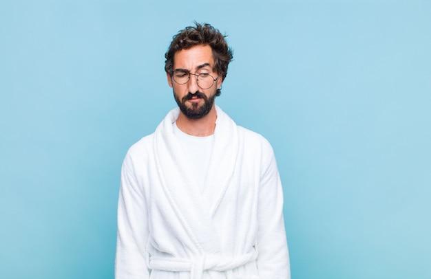 Jovem barbudo vestindo um roupão de banho sentindo-se triste