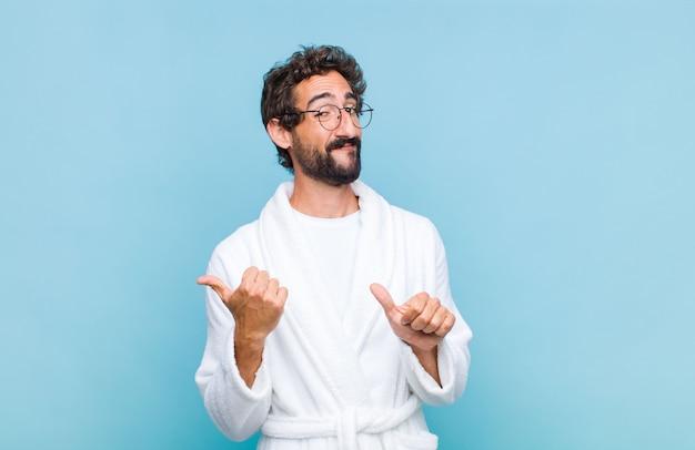 Jovem barbudo vestindo um roupão de banho sorrindo alegremente e apontando casualmente para o espaço ao lado, sentindo-se feliz e satisfeito