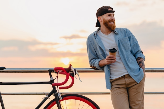 Jovem barbudo viajando de bicicleta no pôr do sol no mar