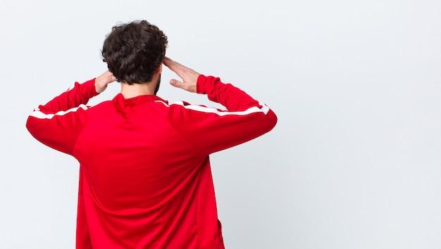 Jovem barbudo vista traseira olhando concentrado, pensativo e inspirado, brainstorming e imaginando com as mãos na testa ao longo da parede do espaço de cópia