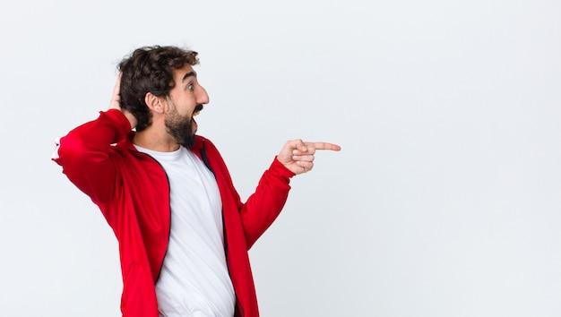 Jovem barbudo vista traseira rindo, olhando feliz, positivo e surpreso, percebendo uma ótima idéia apontando