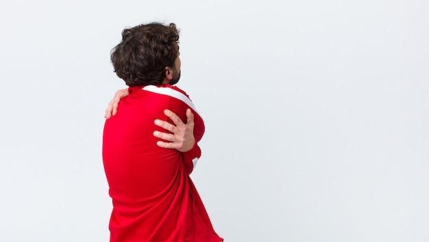 Jovem barbudo vista traseira se sentindo apaixonado, sorrindo, abraçando e abraçando a si mesmo, ficando solteiro, sendo egoísta e egocêntrico contra a parede do espaço da cópia