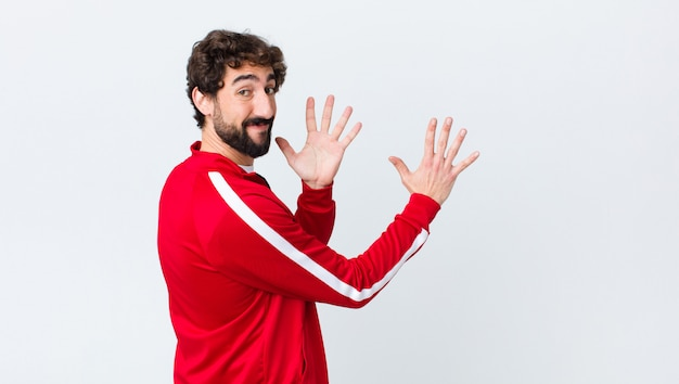 Jovem barbudo vista traseira sorrindo e olhando amigável, mostrando o número dez ou décimo com a mão para a frente, contando na parede do espaço da cópia