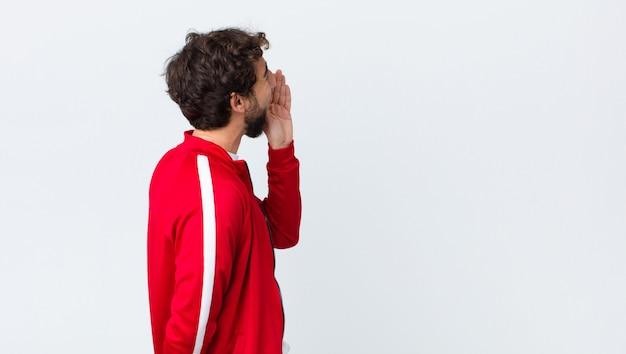 Jovem barbudo vista traseira vista de perfil, olhando feliz e animado, gritando e chamando para copiar o espaço do lado contra a parede do espaço de cópia
