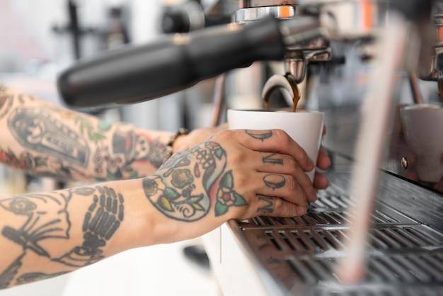 Jovem barista com tatuagens usando a máquina de café no trabalho