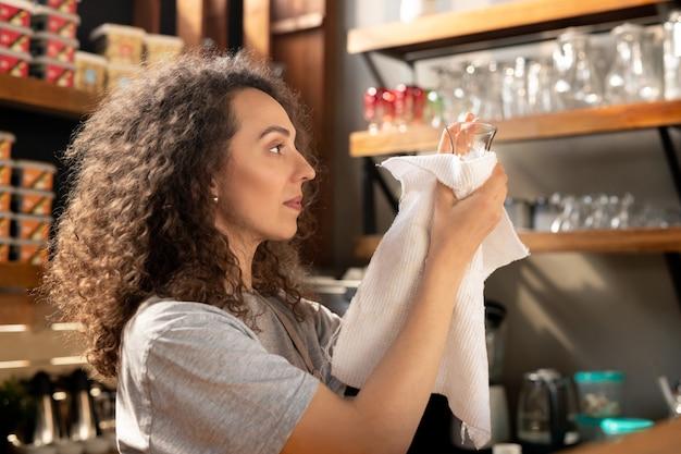 Jovem barista concentrada com cabelo encaracolado, limpando vidro com guardanapo enquanto prepara o copo no bar