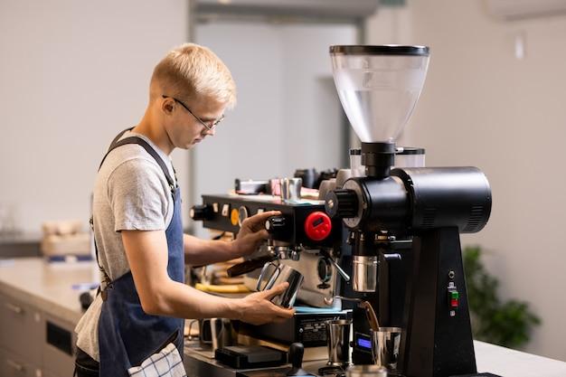 Jovem barista de uniforme com uma caneca de aço em frente à moderna cafeteira enquanto prepara café fresco para os clientes