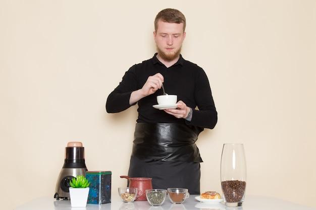 Jovem barista em terno preto com ingredientes e equipamentos de café marrom café sementes em branco