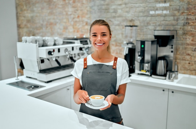 Jovem barista está de pé no balcão de uma cafeteria e sorri, servindo uma xícara de café preparado para um cliente.