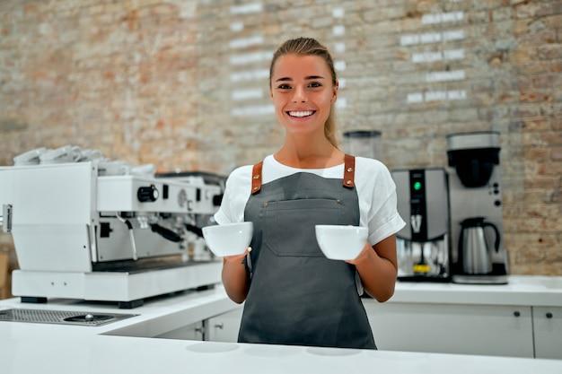 Jovem barista está de pé no balcão de uma cafeteria e sorri, servindo xícaras de café preparado para um cliente.