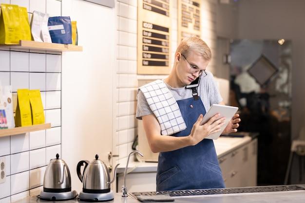 Jovem barista móvel ocupado com touchpad e smartphone atendendo pedidos de clientes online e por telefone