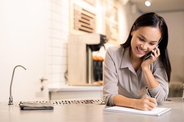 Jovem barista positiva em roupas casuais, consultando clientes no celular enquanto faz anotações no bloco de notas perto do local de trabalho