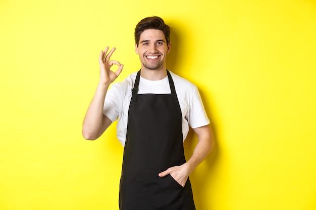 Jovem barista sorridente com avental preto, mostrando sinal de ok, recomendando um café ou restaurante, em pé sobre um fundo amarelo