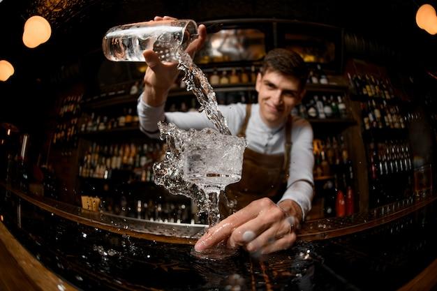 Jovem barman derrama bebida da jarra