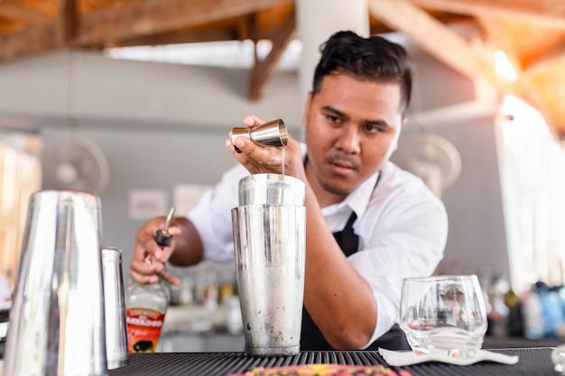 Jovem barman derramando cocktail em um bar, phuket, tailândia