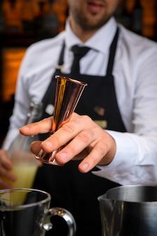 Jovem barman sorridente com um avental preto a preparar vinho quente