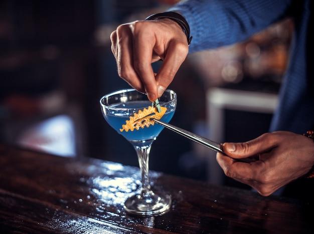 Jovem bartender cria um coquetel enquanto fica de pé perto do balcão do bar em uma boate