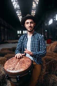 Jovem baterista contra tambor de madeira africano