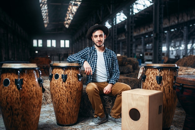 Jovem baterista posa contra tambor de madeira africano