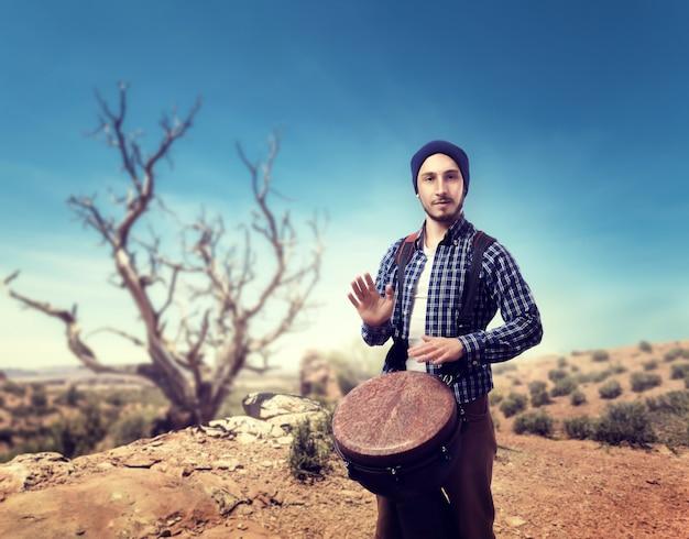 Jovem baterista toca bateria de bongô de madeira no deserto, músico em movimento.