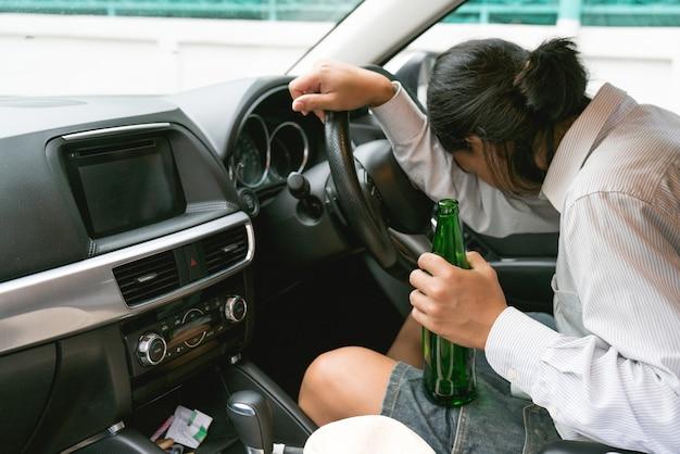 Jovem bêbado dirigindo um carro com uma garrafa de cerveja. não beba e dirija o conceito.