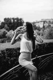 Jovem bebe vinho na varanda de uma casa. preto e branco.