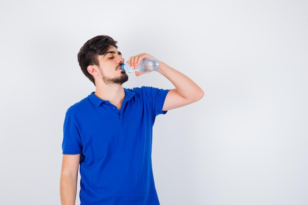 Jovem bebendo água com camiseta azul e olhando sério