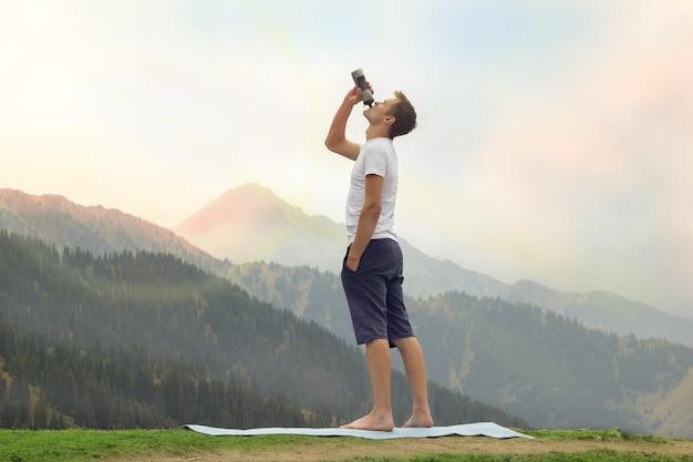 Jovem bebendo água no topo de uma montanha após a prática de ioga