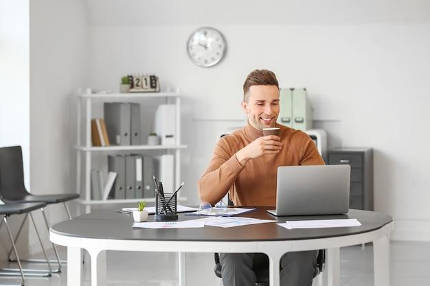 Jovem bebendo café enquanto trabalha no escritório