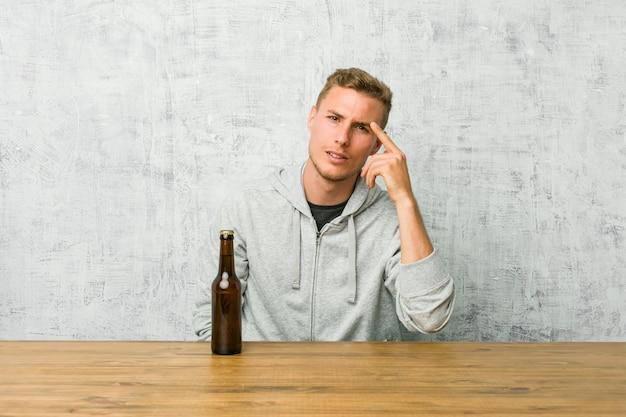 Jovem bebendo uma cerveja em uma mesa, mostrando um gesto de decepção com o dedo indicador.