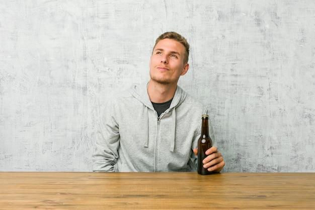 Jovem bebendo uma cerveja em uma mesa, sonhando em alcançar metas e propósitos