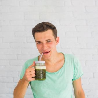 Jovem beber smoothies verdes saudáveis em jar