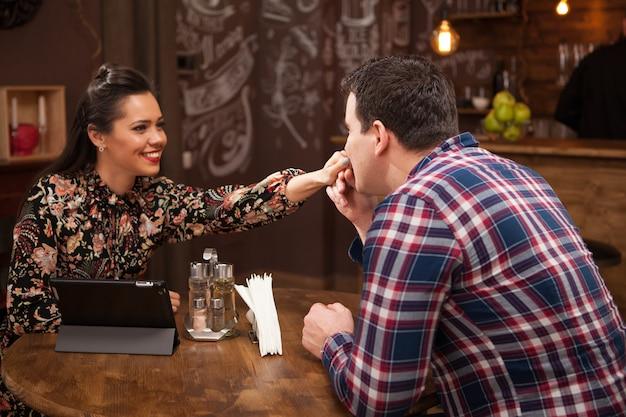 Jovem beijando a mão da esposa em pub vintage. noite na cidade.