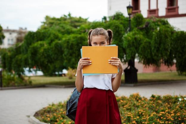 Jovem bela aluna segurando pastas na frente do rosto, ao ar livre
