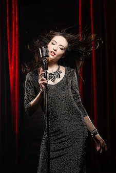 Jovem bela cantora de vestido preto com cabelo solto canta no microfone