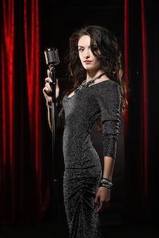 Jovem bela cantora de vestido preto, posando com microfone
