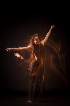 Jovem bela dançarina dançando na parede preta