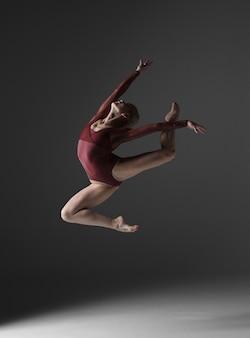Jovem bela dançarina de estilo moderno pulando
