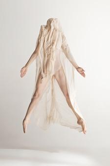 Jovem bela dançarina em maiô bege dançando em cinza