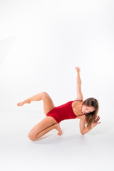 Jovem bela dançarina em maiô vermelho dançando na parede branca