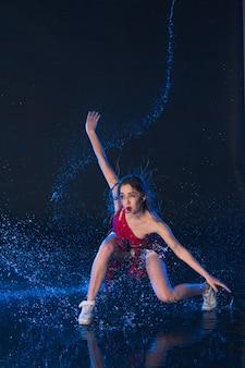 Jovem bela dançarina moderna dançando sob a água cai