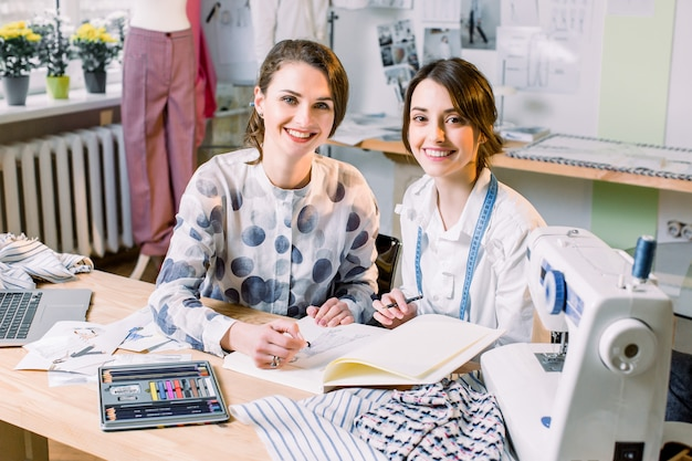 Jovem bela estilista e costureira no ateliê de moda, desenhando o esboço de calças elegantes. o processo de desenhar roupas.