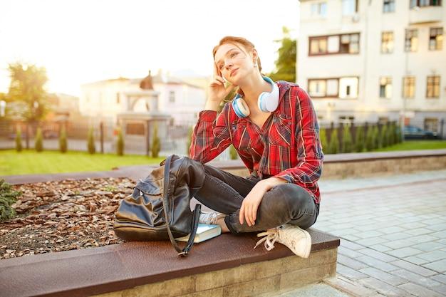 Jovem bela estudante usando uma camisa quadriculada fones de ouvido e uma mochila descansando na rua