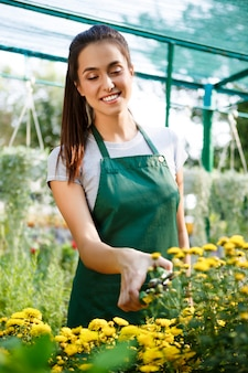 Jovem bela florista cuidando de flores sobre blury.