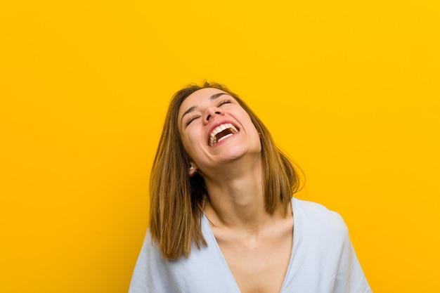 Jovem bela jovem relaxada e feliz rindo, pescoço esticado, mostrando os dentes.