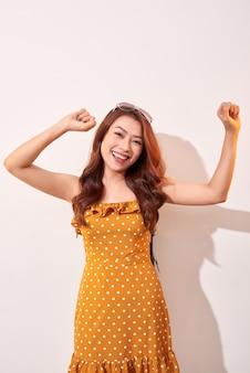 Jovem bela mulher alegre vestindo bolinhas laranja vestido dançando e posando sobre uma parede bege. bom humor. mãos ao ar! pessoas emoções beleza moda conceitos de estilo de vida