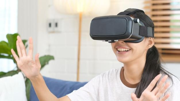 Jovem bela mulher asiática emocionante no fone de ouvido vr, olhando para cima e tentando tocar objetos na realidade virtual em casa, sala de estar, estilo de vida de tecnologia de lazer de pessoas
